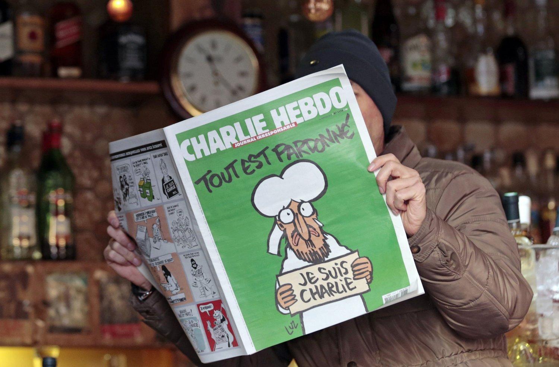 En mann leser den nye utgaven av Charlie Hebdo i en kafé i Nice.