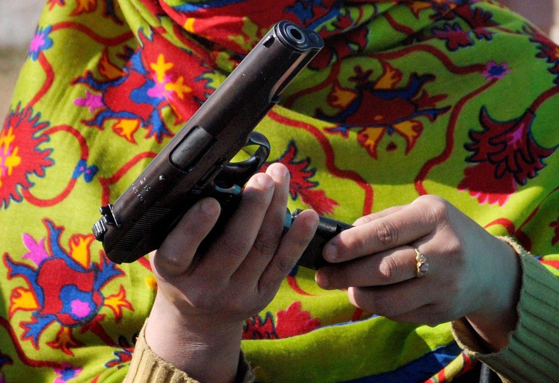 En kvinnelig lærer lader en pistol under et to dager langt våpenkurs i nordvestlige Pakistan.
