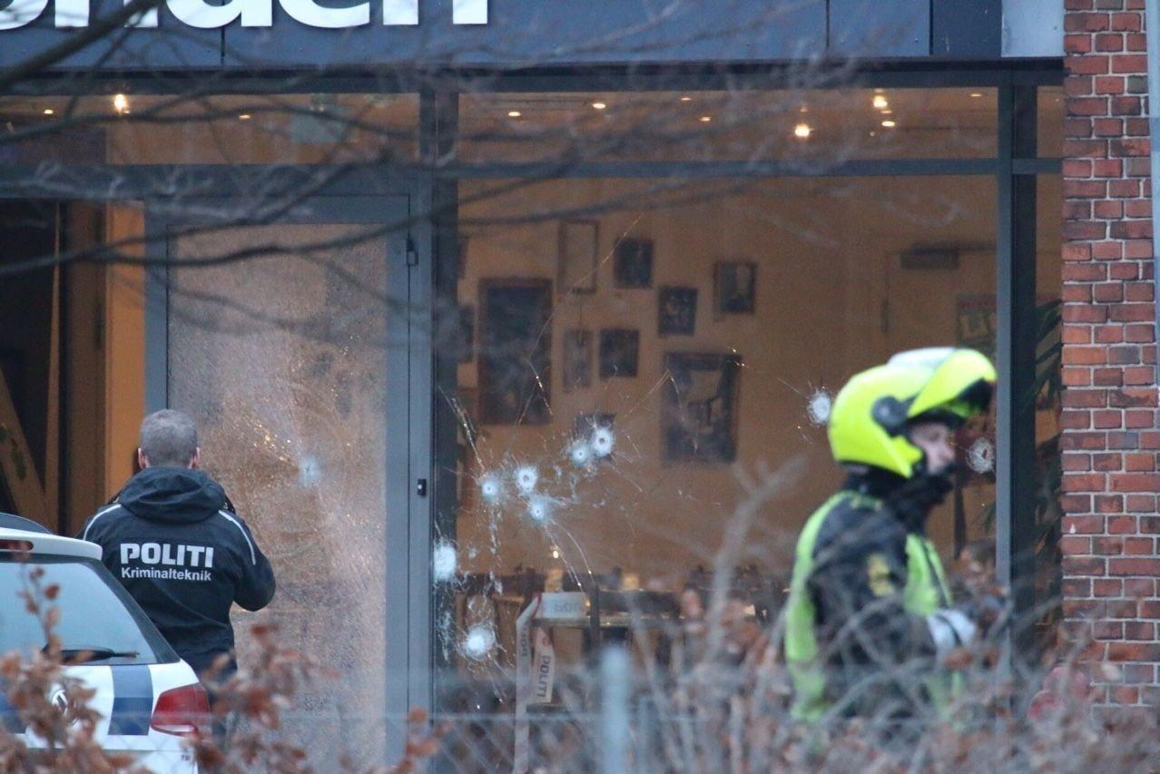 Bildet viser kulehull i vinduet på kulturhuset Krudttønnen i København. Tre politibetjenter ble skadet i skytingen.