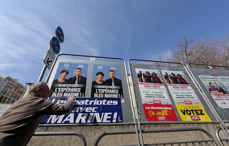VALG: En tilhenger av Nasjonal front henger opp valgplaner med tittelen «Patrioter med Marine», med henvisning partiets leder Marine Le Pen. Foto: Eric Gaillard / Reuters / NTB scanpix