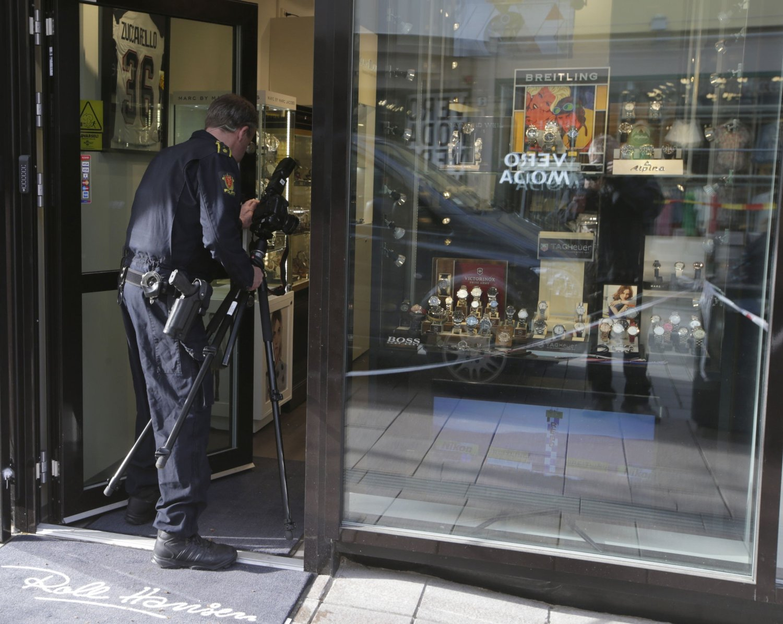 BRUTALT RAN: Polititeknikere inne i urmakerforretningen i Drammen som ble ranet av fire personer fredag ettermiddag. Urmakeren ligger i Nedre Storgate ved Bragenes Torg.