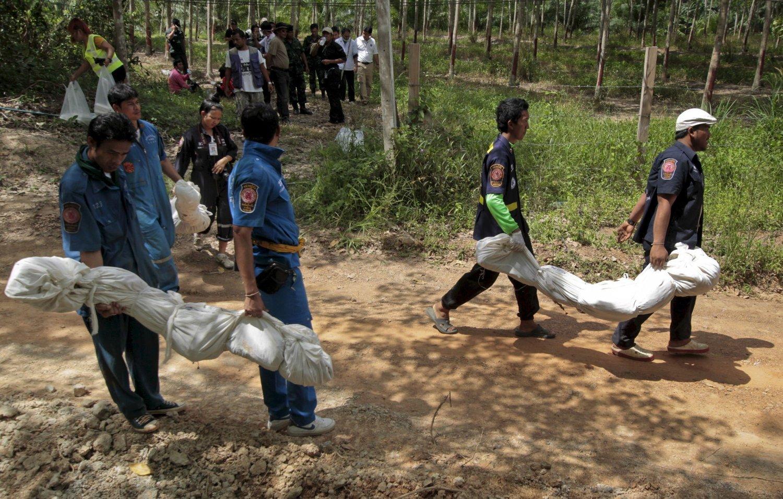 Redningsarbeidere bærer 6. mai ut poser med levningene etter ofrene som ble funnet i en massegrav i provinsen Songkhla sør i Thailand.