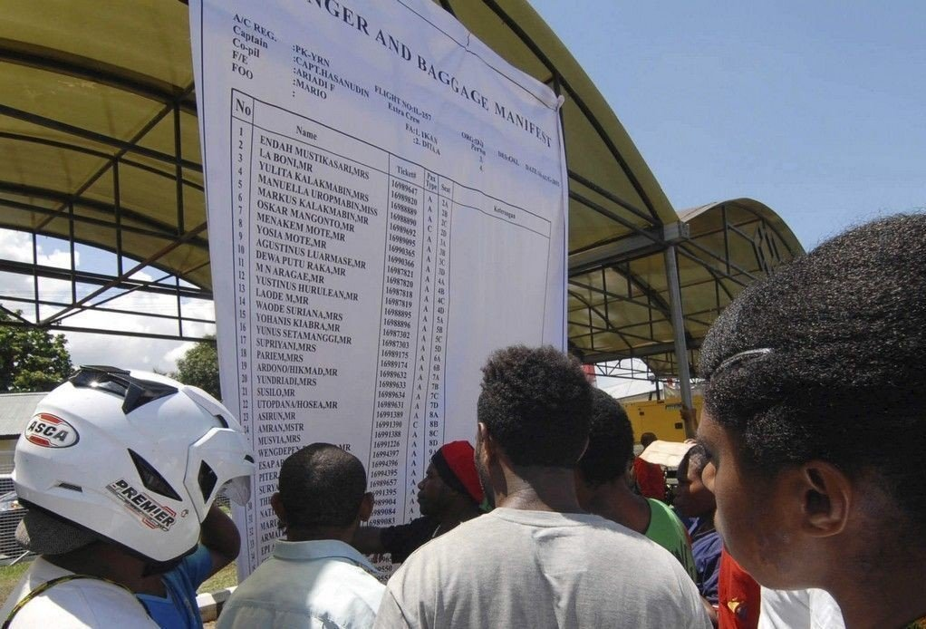 Pårørende studerer passasjerlisten til flyet som styrtet i Papua i Indonesia søndag. Alle 54 som var om bord, er trolig omkommet.