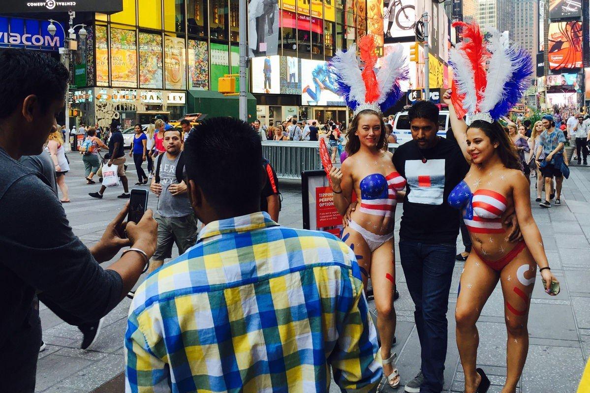 TURISTATTRAKSJON: De toppløse jentene på Times Square ber om penger for å posere sammen med forbipasserende.