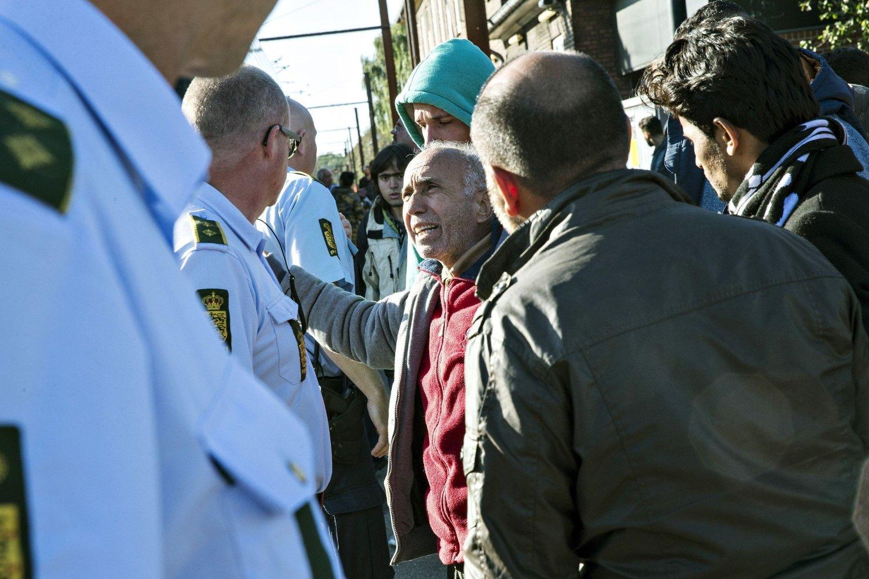 PADBORG: Politiet i samtale med en av migrantene på Padborg stasjon onsdag. En gruppe på 150 personer fikk lov til å reise videre med tog til København etter en natt i Padborg.