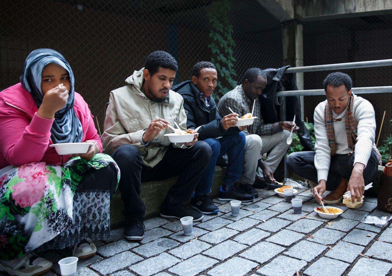 ASYLSØKERE HJELPES AV PRIVATE: Frivillige deler ut mat, som de har fått fra forskjellig restauranter, til asylsøkere utenfor politiets utlendingsenhet på Tøyen.