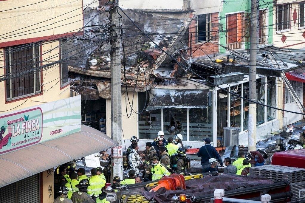 Brannmannskaper slukker brannen som oppsto etter at et småfly styrtet inn i et bakeri i Bogotá søndag.