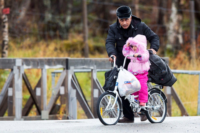 En mann triller en liten jente over grensen fra Russland til Norge på en sykkel uten luft i dekkene.