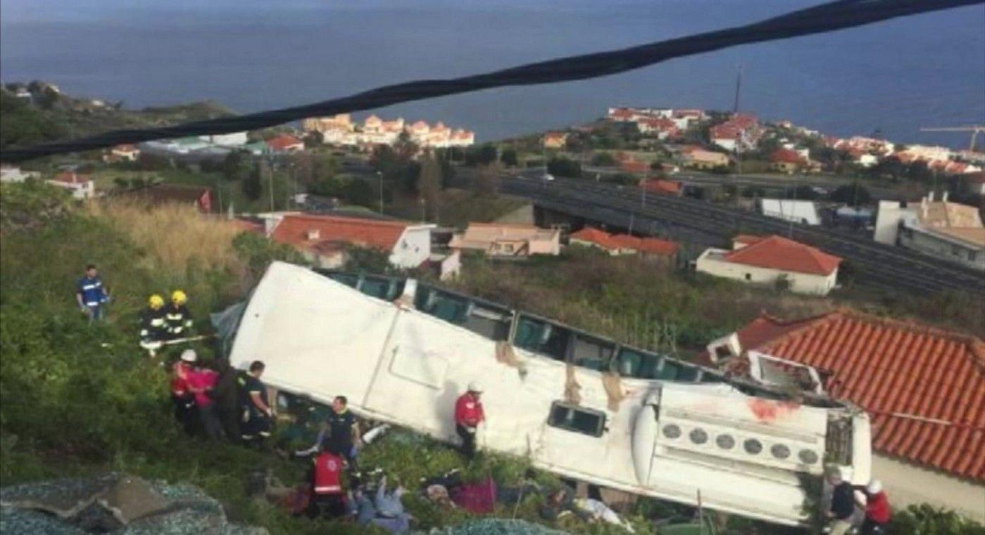 Bussen landet på taket til et hus under skråningen. Foto: (TVI / AP / NTB scanpix)